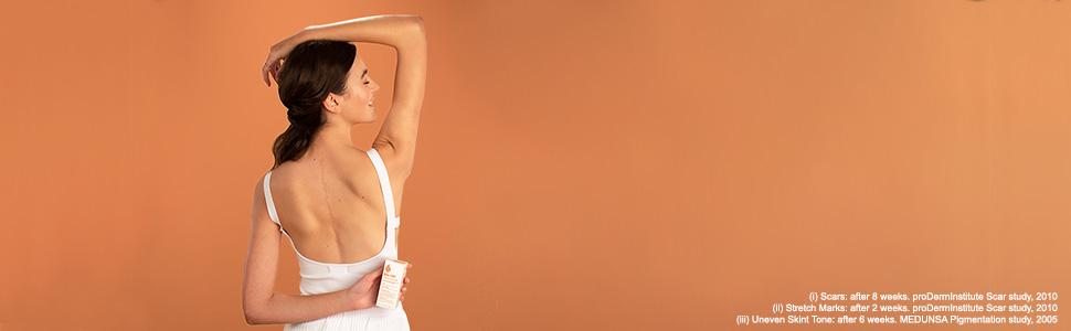 Woman holding a bottle of Bio-Oil Skincare Oil standing in front of an orange wall